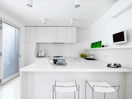 cuisine fond blanc: vue de l'int�rieur d'une cuisine moderne blanc avec des l�gumes sur le wotktop Banque d'images