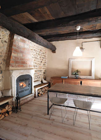 dining table and iron fireplace in rustic living room with wood floor and wood ceiling