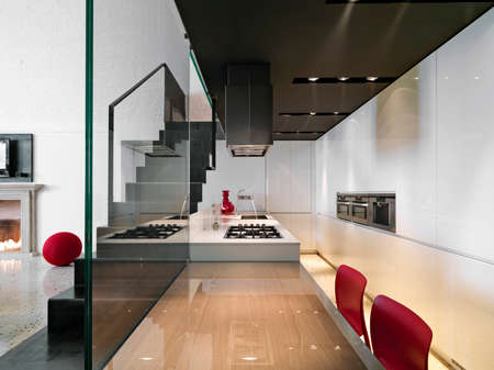 interior view of a modern kitchen with kitchen island ans iron staricase