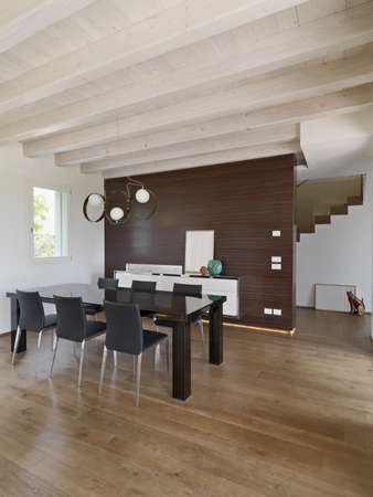 wood ceiling: interior view of a modern livign room with dining table with wood floor and wooden ceiling Stock Photo