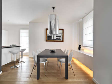dining table and chairs: modern dining room with dining table and wood floor overloking on the ktichen
