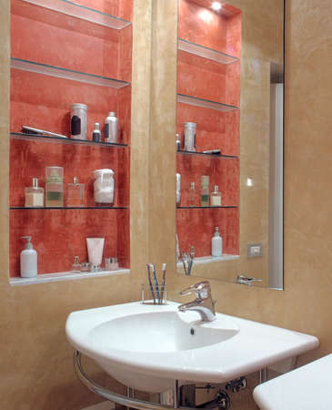 washbasin: foreground of washbasin in a modern bathroom with niche tinted of red and equipped with glass shelves while the wall is tinted of yellow