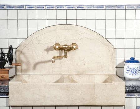 arredamento classico: dettaglio del lavabo in marmo con rubinetto in ottone in cucina la cui parete è rivestita di piastrelle