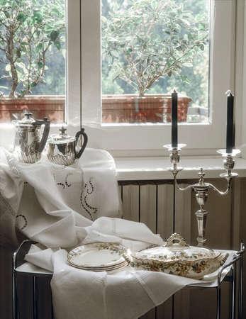 cocina antigua: antiguo barco de salsa, sopera y candelabros de cerca a la ventana