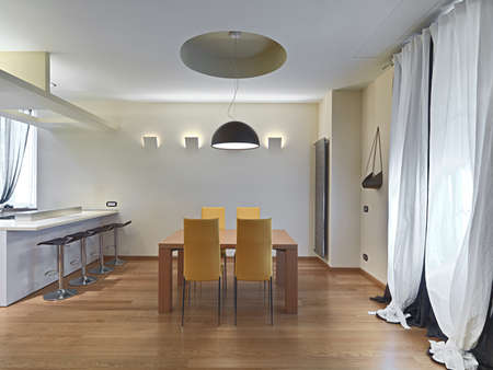 dining table and chairs: modern dining room with yellow leather chairs and wooden table, floor nade of parquet.