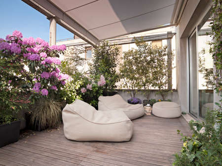 apartment interior: outdoor sofa and armchairs under the tent on the modern terrace with vases of flowwers