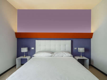 whose: Interior view of a modern bedroom of hotel whose wall  behind to bed is tinted of purple