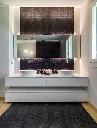 washbasins: interior view of a modern bathroom whose floor is made in mosaic tiles and parquet,  in foreground the white furniture for two washbasins