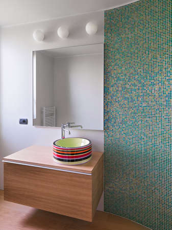 wood furniture: colorful washbasin on the natural wood furniture in the modern bathroom with a wall coated of mosaic tiles Stock Photo