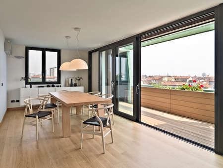 hölzernen Esstisch und Stühle auf dem Dachboden mit Blick auf die Skyline der Stadt, ist der Bodenbelag aus Naturholz