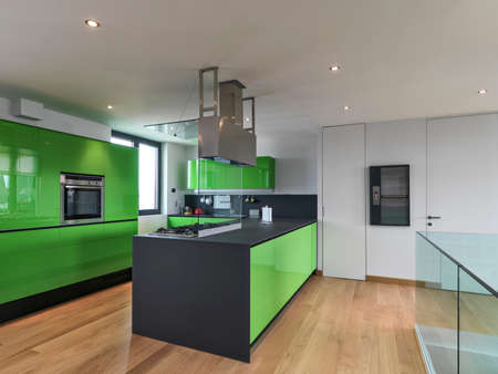attic: green kitchen with kitchen island in the attic room with wood floor Stock Photo