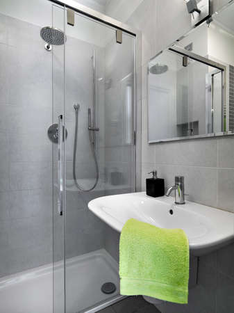 shower cubicle: detail of wassbasin with green towel in a modern bathroom with glass  shower cubicle Stock Photo