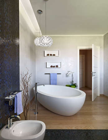 luxury bathroom: foeground of a bathtub in the modern bathroom wgich foor is made of wood