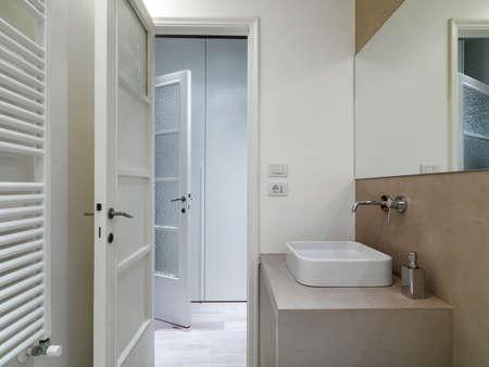 washbasin: detail of washbsin in modern bathroom with door opened on corridor Stock Photo