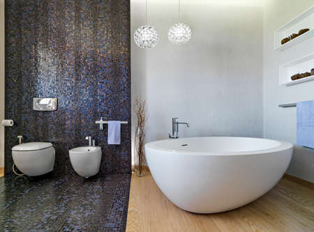 mosaic: interior view of a modern bathroom in foreground the bathtub and sanitay.ware, the floor is made of wood and mosaic tiles.