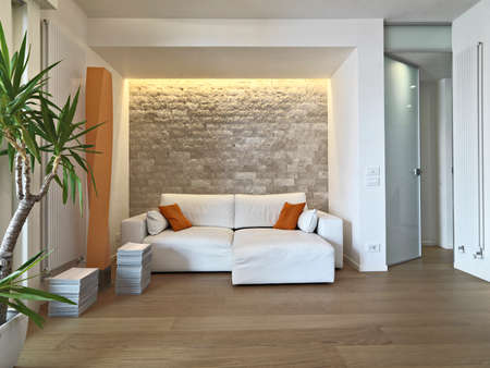 modern apartment: interior view of modern livig room in foreground the leather sofa with orange pillow and wood floor Stock Photo