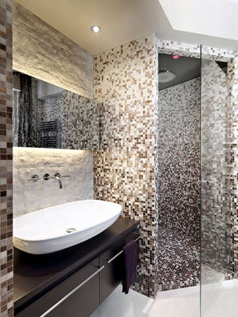 interiors: detail of the sink in a modern bathroom with shower cubicle of masonry covered in mosaic Stock Photo