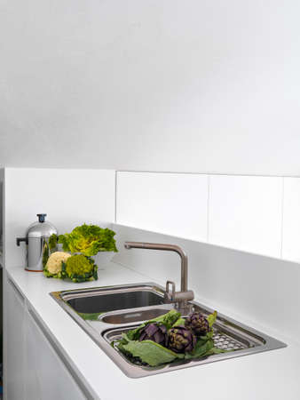 cardunculus scolymus: vegetables on the steel worktop near to faucet in the modern kitchen