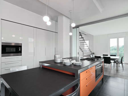 kitchen tool: interior view of a modern kitchen with kitchen island overlooking on the dining room