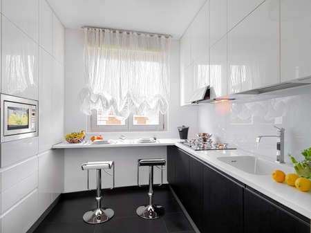 white kitchen: modern white kitchen with two stools near in front of the window