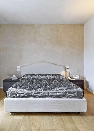 luxurious interior: interior view of a modern bedroom with favric bed and wood floor