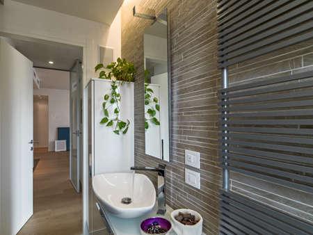 washbasin: modern bathroom with white washbasin and radiator and wood floor Stock Photo