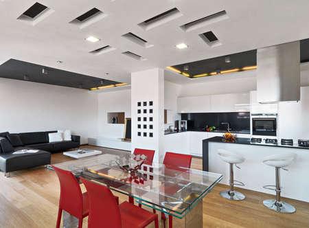 vue de l'intérieur de l'appartement avec plancher de bois au premier plan de la table à manger en verre donnant sur la cuisine moderne et un salon avec canapé en cuir