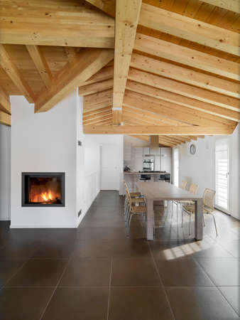 ceiling tile: interior view of a modern lmodernwith dining table,fireplace and wood ceiling overlooking on the kitchen Stock Photo