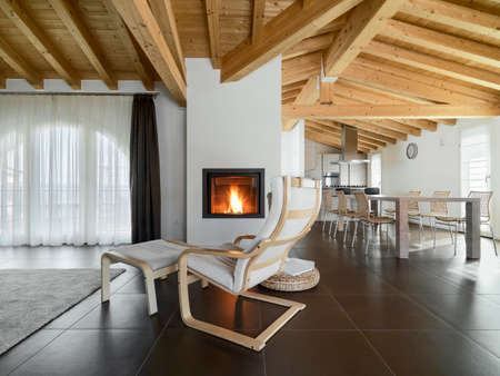 floor tiles: armcahir near to fireplace in the living room of a apartment overlooking on the dining room with wood ceiling Stock Photo