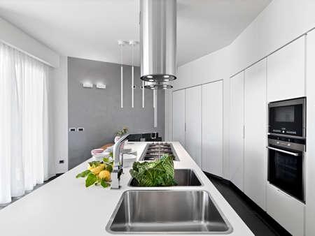 フォア グラウンドでモダンなキッチンの内部ビューはまだワークトップ上に野菜とレモン シンクします。
