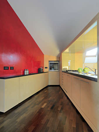attic: interior view of a modern kitchen with wood floor in the attic room whose wall is painted of red Stock Photo