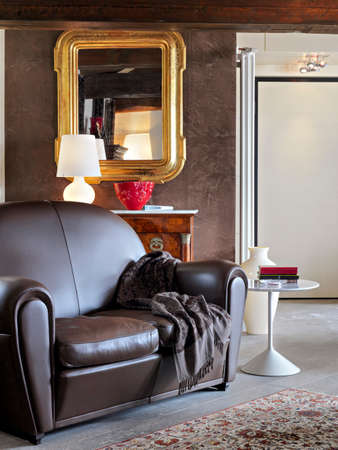 brown leather sofa: foreground of a brown leather sofa in the modern living room overlooking on the entrance