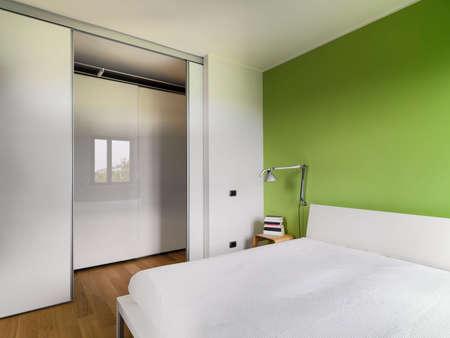 Zwischenansicht eines modernen Schlafzimmer mit Holzboden, dessen Wand aus grünen Blick auf den Flur gemalt