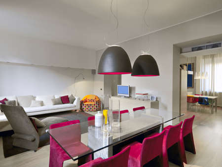 foregronf of glass dining table overlooking on the living room and on the kitchen