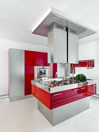 kitchen island: interior view of a modern kitchen with red furniture in foreground the kitchen island whose floor is made of resin