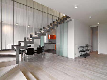 Vordergrund der Eisentreppe in te modernen Wohnzimmer mit Blick auf den dininrg Raum und der Küche, deren Boden ist aus Holz