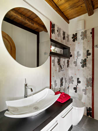 tiled wall: foreground of washbssin in the modern bathroom with wood floor and tiled wall