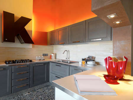 attic room: interior view of a modern kitchen in the attic room whose walls are painted of red Stock Photo