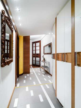 arredamento classico: Vista interna di un moderno corridoio con armadio a muro e pavimenti Archivio Fotografico