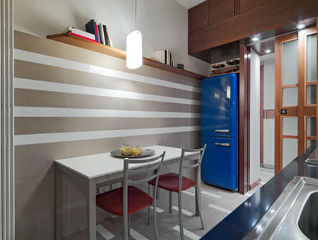 fridge lamp: interior view of a modern kitchen in foregorund the dining table with plat of pears on the itself and the blue fridge