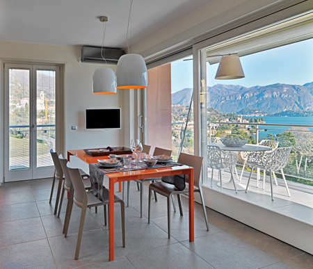 glass table: orange glass dining table in hte modern kitchen overlooking on the terrace and on the lake