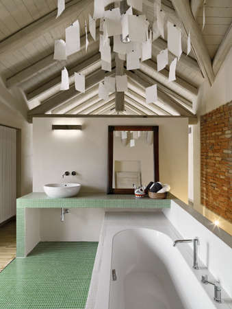 luxurious interior: modern bathroom in the attic with wood ceiling and brick wall