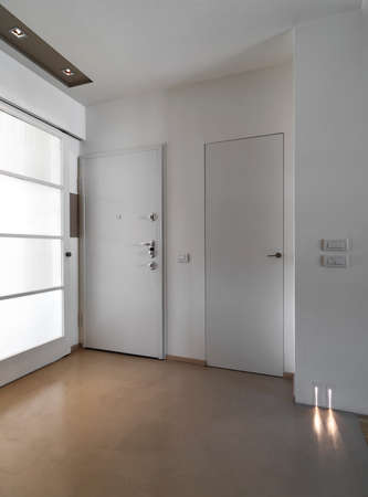 steel floor: interior view of a modern entrance of apartment with white main door and resin floor Stock Photo