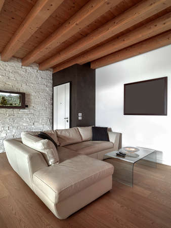 wood ceiling: modern leahter sofa with glass table in the living room near the entrance door, wood floor and wood ceiling