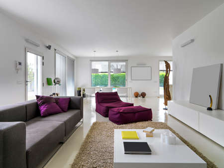 modern dining room: interior view of a modern living room total white in foreground the sofa and purple armchair