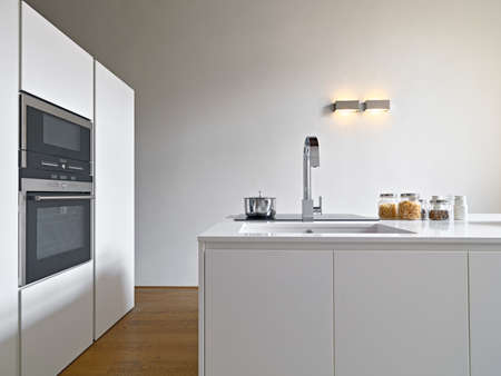 nterior view of a modern kitchen with litchen isalnd, sink and oven the floor is made of wood