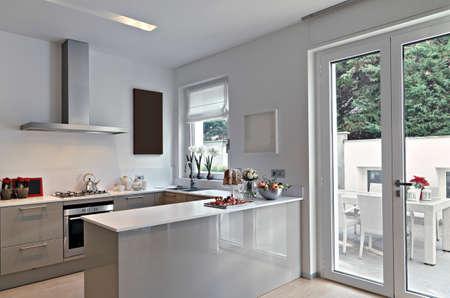 Blick auf eine moderne Küche mit Kochinsel mit Blick auf die Terrasse Standard-Bild - 56652759