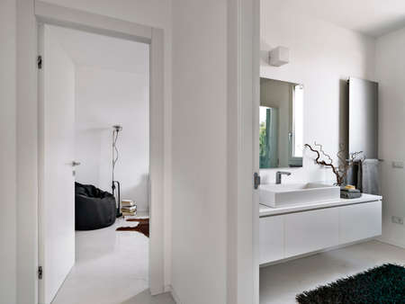 luxury apartment: foreground of washbasin overlooking on the living room in the modern aprtment Stock Photo