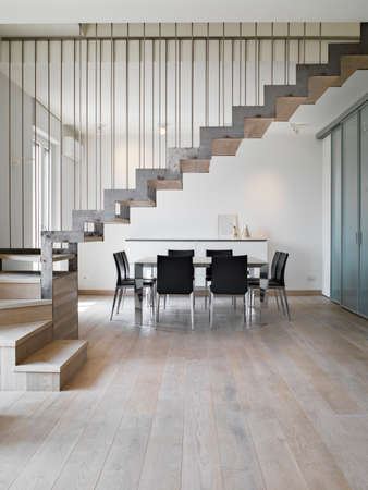 interior view of a modern dining room with dining table and iron staircase the floor isa made of wood Stock Photo
