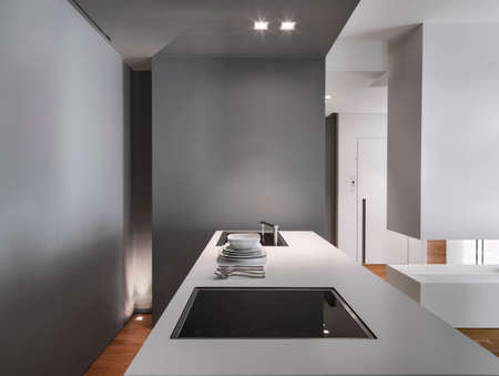 whose: foreground of a modern kitchen island  and cooker in the modern apartment whose floor isa made of wood Stock Photo